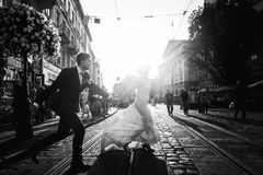 Romantic, fun newlywed couple running across paving road in city Royalty Free Stock Photography
