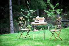 Romantic garden patio. With two chairs, a table and table decorations Royalty Free Stock Photos