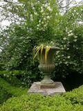 Romantic gardens XIX century. With carved vase and boxwood hedges Stock Photo