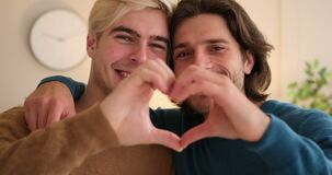 Gay couple embracing and gesturing love sign with hands