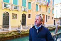 Romantic gaze and tourist in venice, Italy. Romantic gaze, famous architecture, small canal, wooden poles in Venice, in Italy, Europe Stock Photography