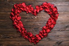 Beautiful bright red rose petals on wooden background. Happy valentines day oliday sales concept. Romantic gesture, love confession, happy valentines day Royalty Free Stock Images