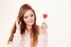 Flirty woman holding red wooden heart on stick. Romantic gestures, valentines gifts ideas concept. Happy flirty woman holding red wooden heart on stick stock images