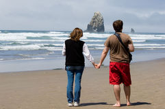 Romantic getaway. Honeymooners walking on famous Cannon beach, Oregon Royalty Free Stock Images