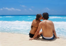 Romantic Getaway. An attractive Young Couple enjoying a moment together on a beautiful, scenic beach Royalty Free Stock Images