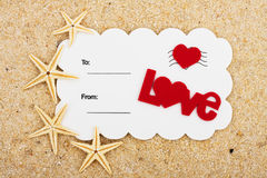 A Romantic Getaway Vacation. A white postcard with a red heart and the word love on a sand background, love postcard Stock Photo
