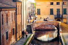 Romantic getaways in italy  warm tone lights at sunset over red bricks old buildings and bridge on the canal of Comacchio Ferrara. Romantic getaways in italy Stock Photography