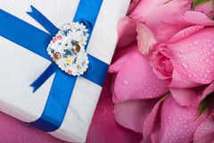 Romantic gift. Wrapped gift with wet roses Royalty Free Stock Photo