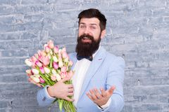 Romantic gift. Macho getting ready romantic date. Tulips for sweetheart. Man well groomed tuxedo bow tie hold flowers. Bouquet. How to be gentleman. Guide for stock photos