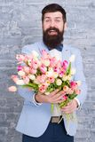 Romantic gift. Macho getting ready romantic date. Waiting for darling. Tulips for sweetheart. Man well groomed wear. Tuxedo bow tie hold flowers bouquet. Invite royalty free stock photo