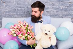 Romantic gift. Romantic man with flowers and teddy bear sit on couch with air balloons waiting girlfriend. Macho ready. Romantic date. Man wear tuxedo bow tie stock photos