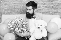 Romantic gift. Romantic man with flowers and teddy bear sit on couch with air balloons waiting girlfriend. Macho ready
