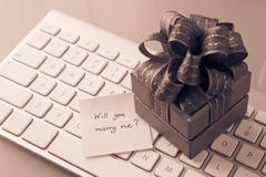 Romantic gift with Marry me? love message, valentine's day conce. Gift box and paper note with romantic love message: Will you marry me? place on keyboard Stock Photo