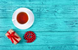 Romantic gift with red bow and cup of tea on wooden background. Gift for woman`s day. White cup of tea. Copy space. Top view Royalty Free Stock Photography