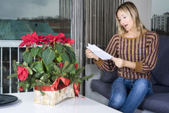 Romantic gift from someone special. Happy blond woman reading the card on the flowers sent to her Stock Photos