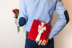 Valentines day gift surprise,man hiding gift and holding red rose bouquet. Romantic gift surprise, man hiding present,gift and holding red roses,couple love royalty free stock image