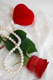 Romantic Gifts. Red rose, pearl necklace and a heart-shaped ring box Stock Photos