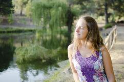 Romantic Girl. Is at the lake watching the horizon. Beautiful lake and forest in the background Stock Photography