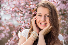 Romantic girl with braces near blossoming tree Royalty Free Stock Photos