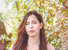 Romantic girl closeup face with close eyes, cherry blossom on the background. Pretty young woman dreaming about something closing eyes, spring time, sinny day Stock Photo