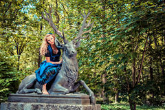 Romantic girl in dirndl sitting on the deer Stock Photography