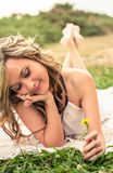 Romantic girl with flower in the hand lying down Stock Image