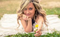 Romantic girl holding flower in the hand lying Royalty Free Stock Photo