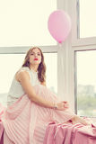 Romantic girl. In long gown sitting by the window royalty free stock images