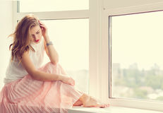 Romantic girl. In long gown sitting by the window stock image