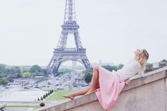 Romantic girl in Paris, fashion woman near Eiffel tower. Romantic girl in Paris, fashion woman looking up near Eiffel tower royalty free stock images