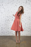 Romantic Girl in  pink dress over brick background looking back Royalty Free Stock Photography