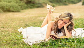 Romantic girl reading a book lying down outdoors Royalty Free Stock Images
