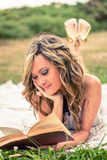 Romantic girl reading a book lying down outdoors Stock Photos