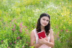 Romantic girl with red book on nature. Romantic girl reading a book on a nature Stock Image