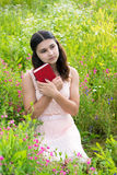 Romantic girl with red book on nature. Romantic girl reading a book on a nature Royalty Free Stock Photos