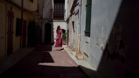 Romantic girl in red polka-dot dress walks through the narrow streets of the old city. Atmospheric street in Antibes