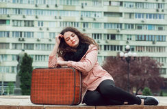 Romantic girl with retro style suitcase sitting outdoor and waiting for transport on big city street. Stock Images