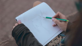 Romantic girl sitting on a bench and drawing pair stock footage