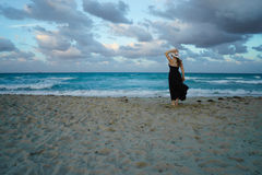Romantic girl standing alone on the beach Stock Photography