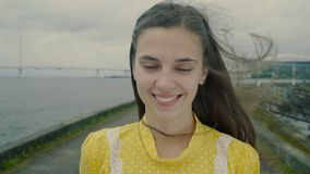 Romantic girl stands on a sea coast and smiles in slow motion stock footage