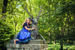 Romantic girl wearing dirndl. And sitting on the deer in the forest stock photography