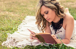 Romantic girl writing in a diary lying down Stock Images