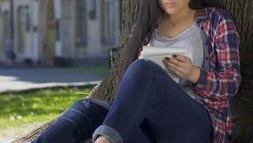 Romantic girl writing love poetry, sitting in shadow of huge tree in summer park. Stock footage stock footage