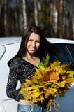 Romantic girl with yellow leaves and white car Stock Images