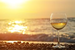 Romantic glass of wine sitting on the beach at colorful sunset Glasses of white wine against sunset, white wine on the sky backgro. Und with clouds stock photography