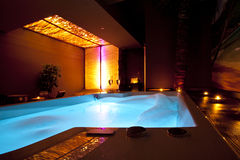 Romantic golden foam SPA bath. Romantic SPA with changing LED lights with wild ambient with candles, palms, champagne and golden walls. Nice jacuzzi with foam Royalty Free Stock Images