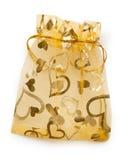 Romantic golden gift bag Stock Images