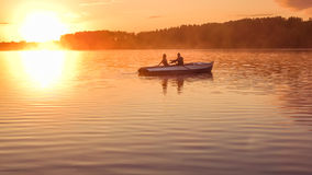 Romantic golden sunset river lake fog loving couple small rowing boat date beautiful Lovers ride during Happy woman man together r Stock Images