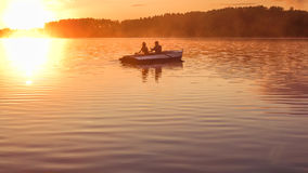 Romantic golden sunset river lake fog loving couple small rowing boat date beautiful Lovers ride during Happy woman man together r Royalty Free Stock Photography