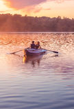 Romantic golden sunset river lake fog loving couple small rowing boat date beautiful Lovers ride during Happy woman man together r Royalty Free Stock Image